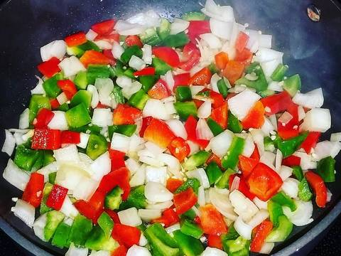 In a large pot, heat up a little oil, about 1 Tbsp. over medium high heat. Once oil is hot add in your peppers and onion. Cook about 4 minutes.