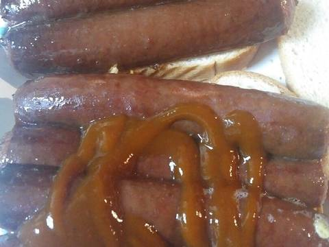 Add two split sausages to each part of the eggs and Heinz 57 steak sauce on top of the sausages.