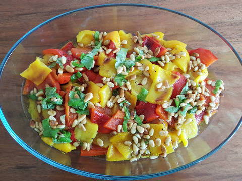 Put the bell peppers and pine nuts in the dressing and top with basil.