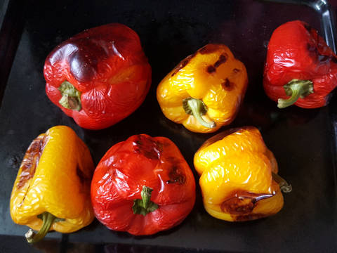 Preheat oven to 180 °C (350 °F). Wash bell peppers and place on a baking tray. Bake until the skin of the bell peppers becomes almost black (turn peppers from time to time).