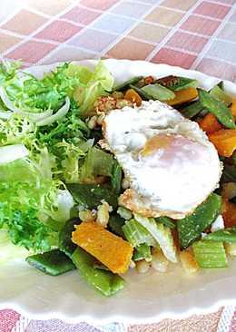 Huevo fritode coral sobre verdura y escarola