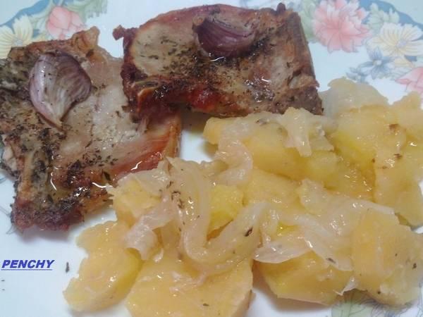 Chuletas de cerdo asadas en cama de patatas y cebollas especiadas
