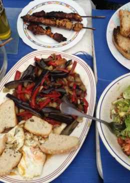 Brochetas de pollo, ensalada con pipas, pisto y dos huevos fritos