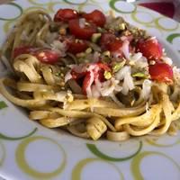 Pasta al pesto con tomates cherry, queso curado y pistachos