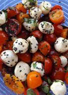 Ensalada de tomatitos variados y boconccini con jamón crujiente y sésamo negro