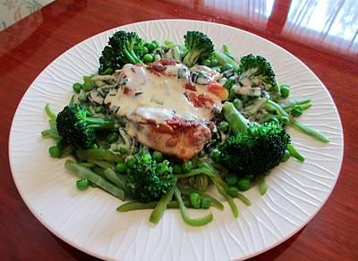 Muslo de pollo sobre verduras al vapor y salsa con ajos tiernos