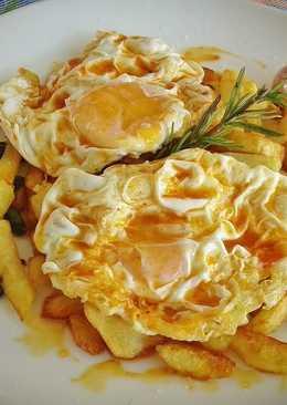 Huevos fritos con patatas, ajos enteros y pimientos de padrón