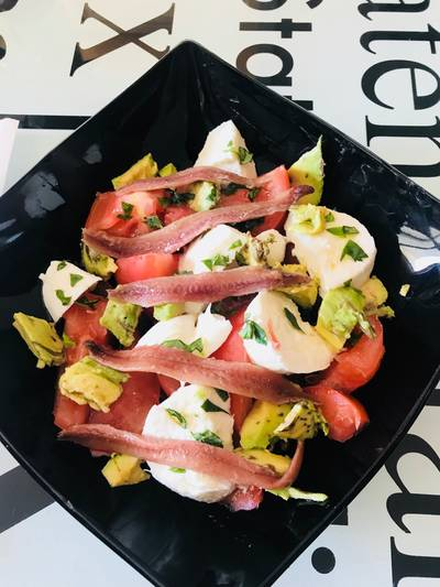 Ensalada de tomate, mozzarella, aguacate y anchoas, con albahaca fresca y regada con Aceite oliva