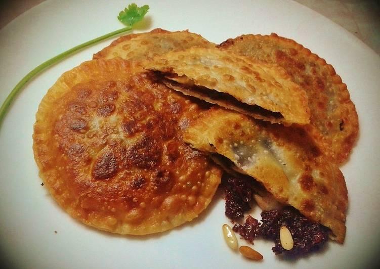 Empanadillas de morcilla y queso de cabra, con miel y piñones