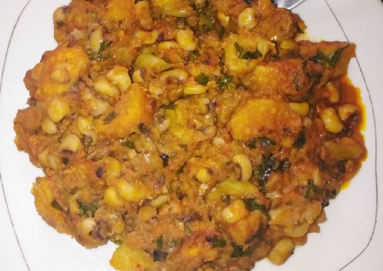 African Food Delicious beans and ripe plantain porridge with scent leaves