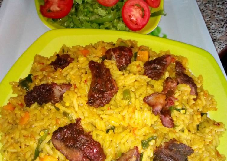 Jollof rice with roasted meat and salad