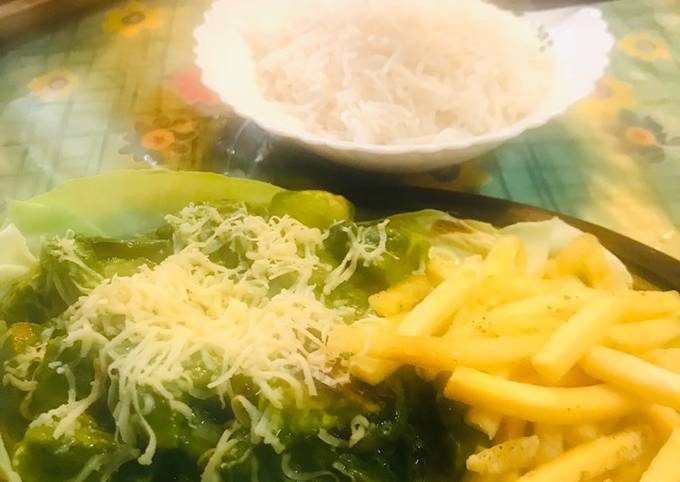 Pesto sauce boiled veggies with French fries and steamed rice in a sizzling plate