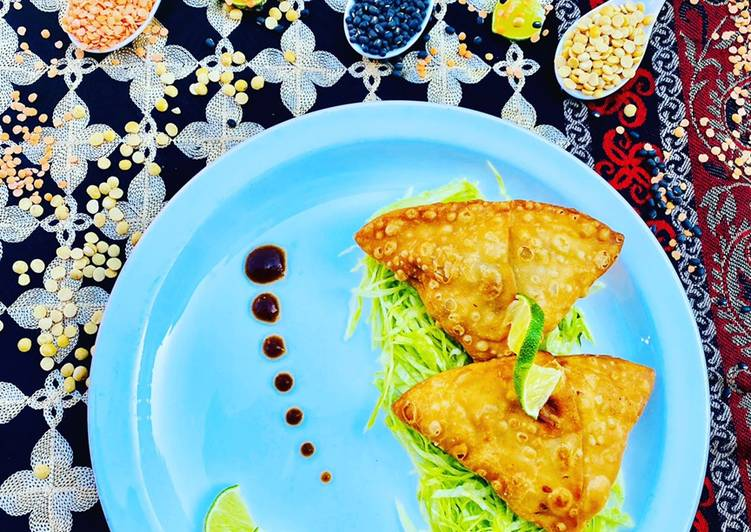 Homemade Fresh Samosa served on bed of lettuce with tamarind sauce and limes