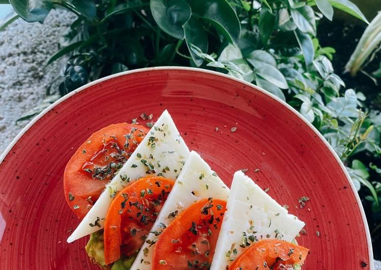 Tostada de pan de hogaza con aguacate, tomate, queso semi y orégano