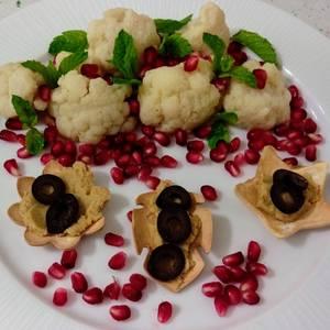 Ensalada de coliflor con granada y menta y flores con hummus y aceitunas