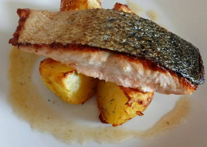 Pan fried salmon on an open jacket with dill and butter