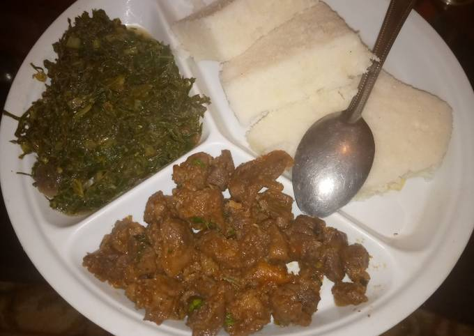 Ugali served with marinated beef and steamed spinach