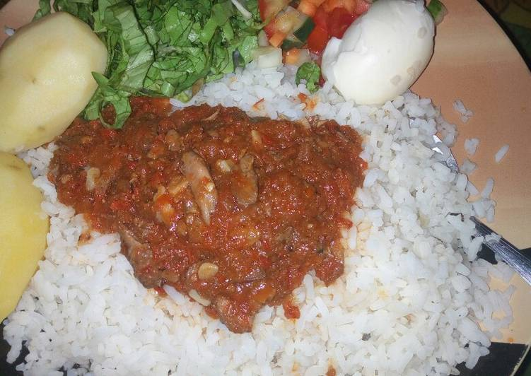 Rice and stew with boiled potatoes,egg and salad