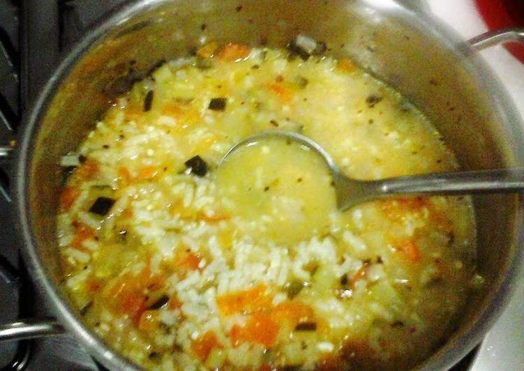 Risotto rice soup with green zucchini and tomato