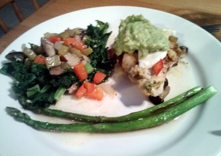 Tasty And Delicious of Garden Chicken with Marinated Fresh Mozeralla, Garlic Kale, butter seared Asparagus and Guacamole topping