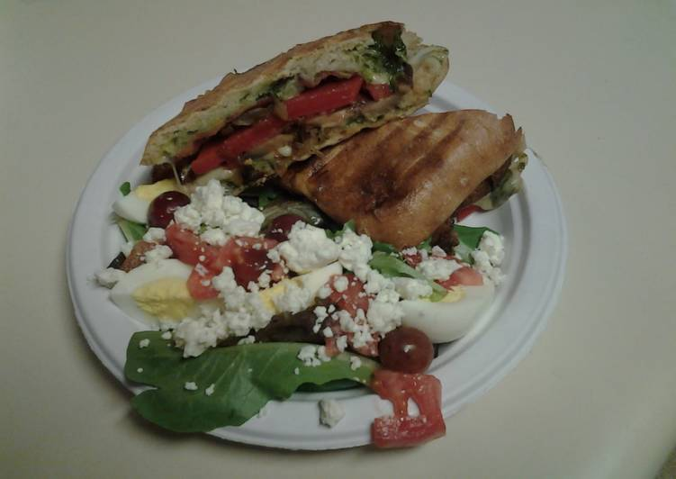 Ciabata bread, pesto, pepper, and cheese sandwich with spinach salad