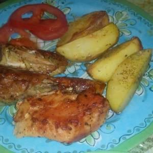 Pollo sazonado al horno con papas y tomate