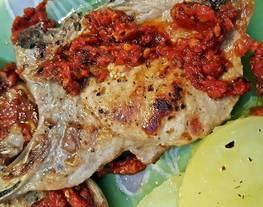 Chuleta de cerdo con salsa de tomate aromatizada al ajo