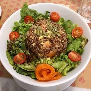 Timbal de Quinoa 3 semillas con palta y salmón junto a lechuga, tomate cherry y semillas de zapallo