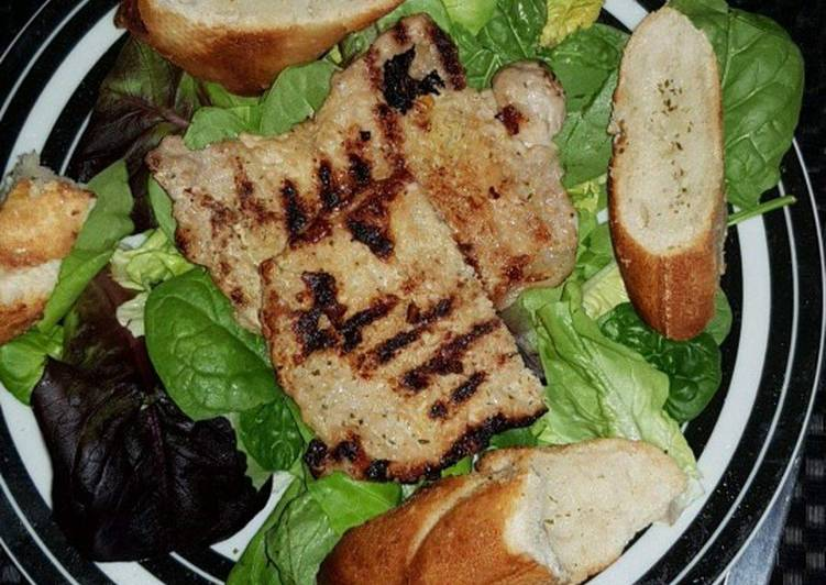 Grilled pork with salad and garlic bread
