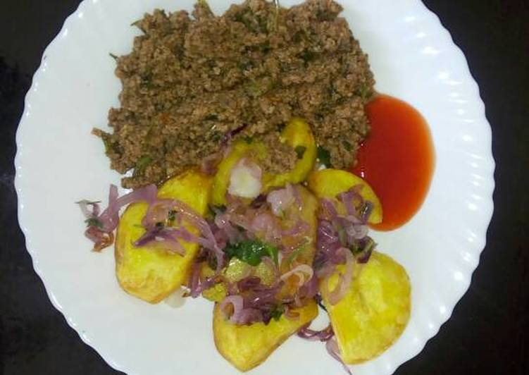 Roast Potatoes garnished with onions and coriander served with minced meat