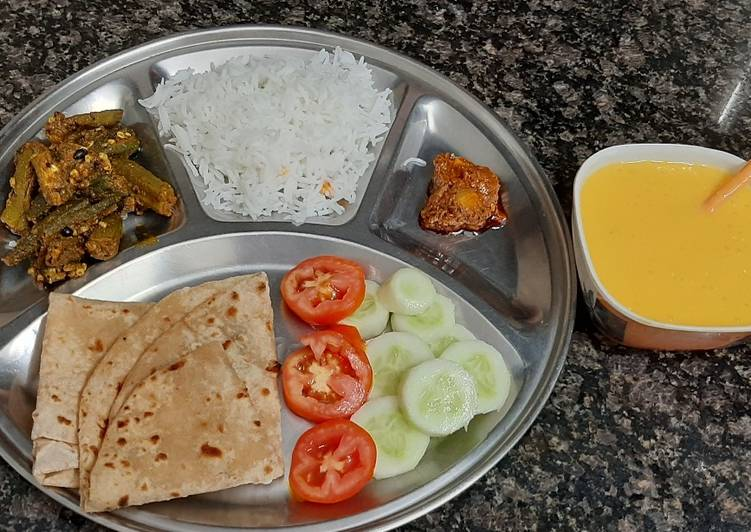 Simiple veg thali lunch with bhindi, roti, rice, mango juice