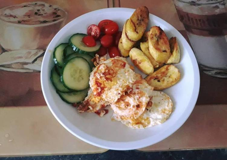 Fried plantain with fried egg served with cucumber and fresh tomatoes