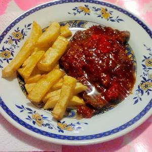 Bistec en salsa de tomate con papas fritas