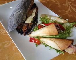 Bocata de calamares con pan negro con tinta de calamar y cucuruchos de calamares con ensalada