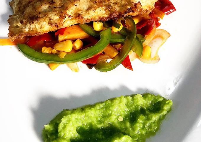 Deep fried fish fillet on a bed of sautéed vegetables & pea purée