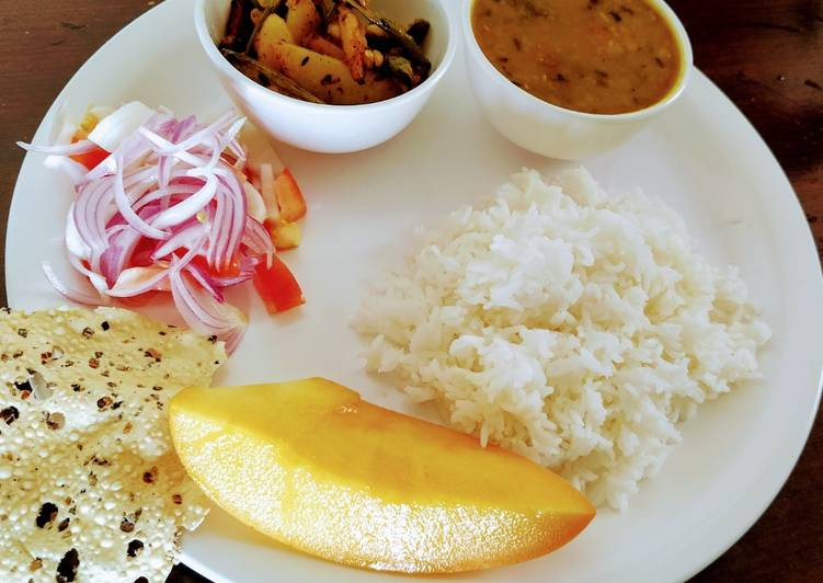 Veg thali with rice, mix dal tadka, aloo patal stir fry and salad