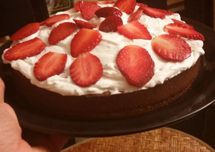 Moist chocolate cake topped with whipped cream and strawberries