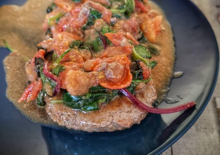 Hamburger con pomodori freschi e insalata mista cotti in padella