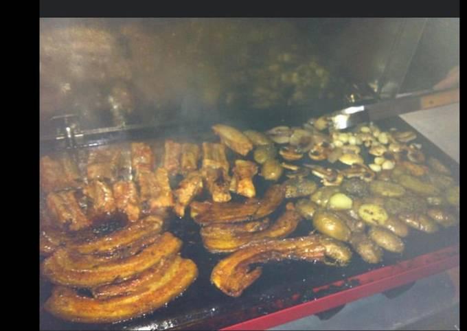 Plancha au lard et travers de porc marinés pommes de terre courgettes et oignons