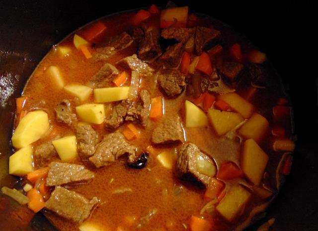 Заливаем жаркое 3 стаканами воды, насыпаем томатную пасту.